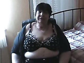 Short haired granny is playing with her huge boobies