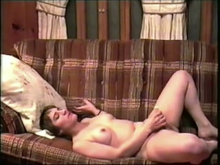 White French wife on the couch masturbates with a small dildo